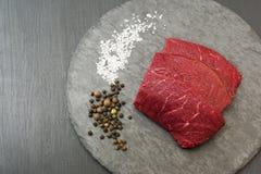 Nytt och rått kött Skivade biffar i rad som är klara att laga mat Svart svart tavla för bakgrund och svart stenplatta royaltyfri foto
