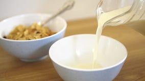 Nytt och sunt kraxa mjölkar långsamt att hälla i viten skrålar Sund mat och flingor på bakgrunden serving stock video