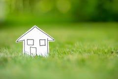 Nytt pappers- hus i gräs Fotografering för Bildbyråer