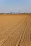 Nytt plöjt fält med cityscape av Frankfurt - f.m. - strömförsörjning på horisonten Arkivfoton