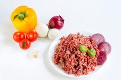 Nytt rått finhackat nötkött i ett vitt plattaslut upp med peppar, löken och tomater, rå ingredienser för välfyllda peppar royaltyfri fotografi