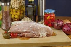 Nytt rått griskött på en skärbräda med grönsaker Arkivbilder