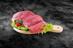 Nytt rått grisköttskinkakött dekorerade med grönsaker på köksbordet plus den snabba banan royaltyfria foton