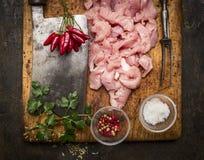 Nytt rått huggit av kalkon, köttköttyxa, köttgaffel, salt, peppar, varma peppar och nya örter på en träskärbräda på lantlig w Royaltyfri Fotografi