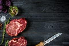 Nytt rått nötkött med basilika och en kvist av rosmarin med kniven med ett trähandtag på svart träbakgrund Top beskådar Arkivfoto