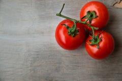 Nytt rött - läckra tomater på en gammal trätabletop Royaltyfria Foton