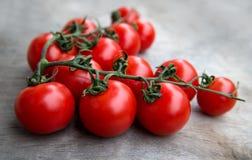 Nytt rött - läckra tomater på en gammal trätabletopbackgrou Royaltyfria Bilder
