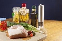 Nytt rått griskött på en skärbräda med grönsaker Arkivbild