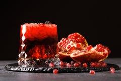 Nytt sammanpressad granatäpplefruktsaft med iskuber på en svart bakgrund Mogen, saftig, organisk och fördelgranatröttfrukt arkivbilder