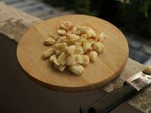 Nytt skalad och slagen vitlök på träskärbräda med kniven - gammal lägenhetbalkong royaltyfri bild