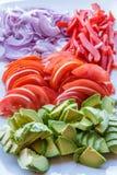 Nytt skivad avacado, tomat och lök på portionplattan Royaltyfria Foton