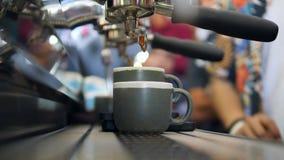 Nytt svart kaffe som häller från yrkesmässig maskinutmatare i koppar 4K slowmotion makro lager videofilmer