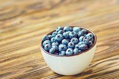 Nytt valda blåbär i den vita bunken Saftiga och nya blåbär på den lantliga tabellen Blåbär på träbakgrund Blåbär Royaltyfri Bild
