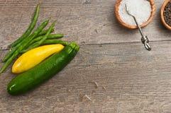 Nytt valda grönsaker med wood bunkar av havet saltar, och ny peppar konserverar Royaltyfria Foton