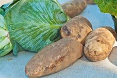 Nytt valt, markerade kålhuvudet och potatisar på bönder arkivfoto