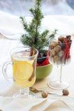 Nytt varmt grönt te i den glass koppen med citronen och kanel, chokladkakor i korg och muttrar och kanel Royaltyfria Bilder