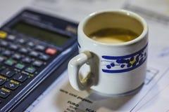 Nytto- räkningar, kaffe och räknemaskin Arkivbild