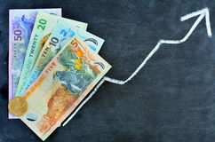 NZ Dollar banknotes with upward trend arrow Stock Photo