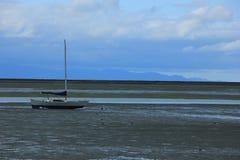 NZ, Südinsel, einsames Boot auf dem Strand während der Ebbe Lizenzfreie Stockbilder