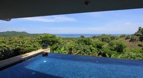 Oändlighetspöl av ett lyxigt hus med sikten av rainforesten och stranden, Costa Rica Arkivbild