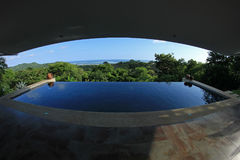 Oändlighetspöl av ett lyxigt hus med sikten av rainforesten och stranden, fisheyeperspektiv, Costa Rica Fotografering för Bildbyråer