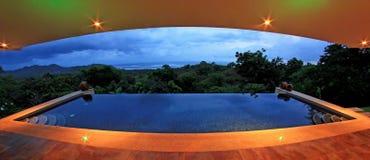 Oändlighetspöl av ett lyxigt hus med sikten av rainforesten och stranden, fisheyeperspektiv, Costa Rica Royaltyfria Foton