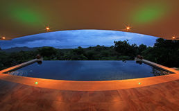 Oändlighetspöl av ett lyxigt hus med sikten av rainforesten och stranden, fisheyeperspektiv, Costa Rica Royaltyfri Bild