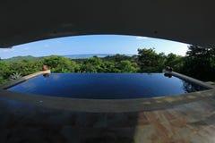 Oändlighetspöl av ett lyxigt hus med sikten av rainforesten och stranden, fisheyeperspektiv, Costa Rica Royaltyfri Fotografi