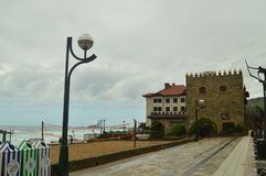 Oändligt maritimt går av Zarauz på en regnig dag med stark vind som orsakas av den tillfälliga Hugo With Hotel Castle Restaurant  royaltyfri foto