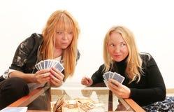 Oärlighet - en listig flicka som fuskar hennes vän, medan spela kortspelet för pengar Royaltyfri Bild