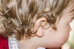 Oído de una niña con un pendiente fotos de archivo libres de regalías
