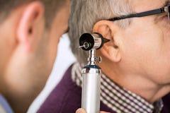 Oído del doctor Examining Patient fotografía de archivo