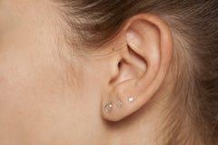 Oído femenino con los pendientes imagen de archivo libre de regalías