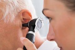 Oído femenino del ` s del doctor Examining Patient imagen de archivo