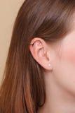Oído humano del primer con los pendientes Fotos de archivo libres de regalías