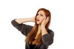 Oídos adolescentes enojados de la cubierta de la mujer con las manos Fotos de archivo
