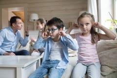 Oídos cercanos del muchacho y de la muchacha para no oír a padres el pelear fotos de archivo libres de regalías