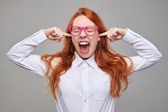 Oídos cerrados de la muchacha furiosa con los dedos índices Imagenes de archivo
