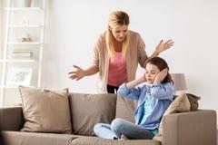Oídos cerrados de la muchacha para no oír a la madre enojada en casa Fotografía de archivo