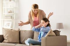 Oídos cerrados de la muchacha para no oír a la madre enojada en casa Imágenes de archivo libres de regalías