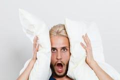 Oídos cerrados del hombre enojado con las almohadas Foto de archivo