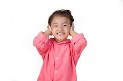 Oídos cerrados del niño pequeño con sus manos, aisladas imagenes de archivo