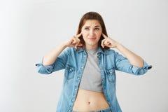 Oídos cerrados descontentados de la muchacha hermosa joven con los fingeres sobre el fondo blanco Imágenes de archivo libres de regalías