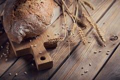 Oídos crujientes del pan y del trigo del multigrain fresco en un de madera rústico Foto de archivo