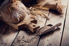 Oídos crujientes del pan y del trigo del multigrain fresco en un de madera rústico Imagenes de archivo