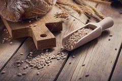 Oídos crujientes del pan y del trigo del multigrain fresco en un de madera rústico Fotos de archivo