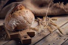 Oídos crujientes del pan y del trigo del multigrain fresco en un de madera rústico Imágenes de archivo libres de regalías