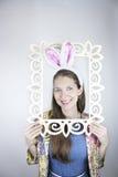 Oídos de conejo hermosos de la mujer que llevan joven y presentación con el marco Fotografía de archivo