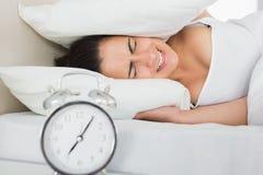 Oídos de la cubierta de la mujer con la almohada en cama Imagen de archivo