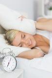 Oídos de la cubierta de la mujer con la almohada y el despertador en la tabla Imagenes de archivo